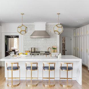 Пример оригинального дизайна: большая п-образная кухня-гостиная в стиле современная классика с белыми фасадами, разноцветным фартуком, фартуком из стеклянной плитки, техникой из нержавеющей стали, островом, врезной раковиной, фасадами в стиле шейкер, светлым паркетным полом, мраморной столешницей и коричневым полом
