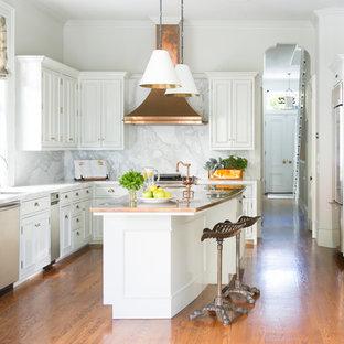 Foto på ett vintage u-kök, med en undermonterad diskho, luckor med infälld panel, vita skåp, bänkskiva i akrylsten, vitt stänkskydd, stänkskydd i sten, rostfria vitvaror, mellanmörkt trägolv, en köksö och brunt golv