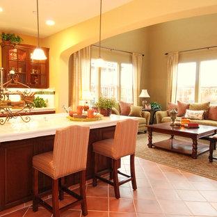 ロサンゼルスの地中海スタイルのおしゃれなキッチン (アンダーカウンターシンク、ガラス扉のキャビネット、濃色木目調キャビネット、タイルカウンター、白いキッチンパネル、シルバーの調理設備の、磁器タイルの床) の写真