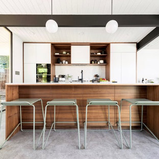 Inspiration for a midcentury galley open plan kitchen in San Francisco with flat-panel cabinets, white cabinets, white splashback, mosaic tile splashback, panelled appliances, with island, grey floor and white benchtop.