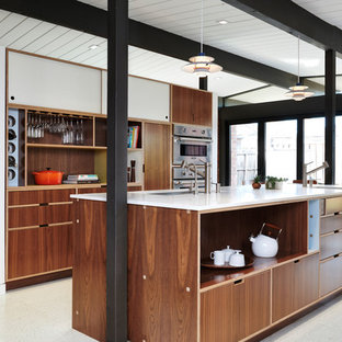 This is an example of a midcentury galley kitchen in San Francisco with an undermount sink, flat-panel cabinets, dark wood cabinets, stainless steel appliances, with island, white floor and white benchtop.