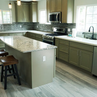 Photo of a mid-sized transitional l-shaped eat-in kitchen in San Francisco with a double-bowl sink, green cabinets, quartzite benchtops, grey splashback, stainless steel appliances, plywood floors, with island, grey floor, recessed-panel cabinets, matchstick tile splashback and white benchtop.