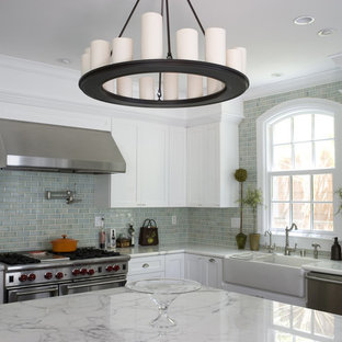 Example of a classic l-shaped dark wood floor open concept kitchen design in San Francisco with a farmhouse sink, shaker cabinets, white cabinets, marble countertops, blue backsplash, ceramic backsplash, stainless steel appliances and an island