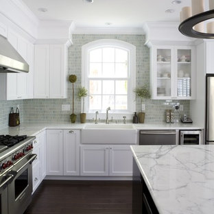 Пример оригинального дизайна: кухня среднего размера в классическом стиле с раковиной в стиле кантри, техникой из нержавеющей стали, темным паркетным полом, белой столешницей, фасадами в стиле шейкер и белыми фасадами