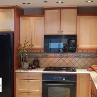 Southwestern eat-in kitchen inspiration - Example of a southwest l-shaped eat-in kitchen design in San Luis Obispo with an integrated sink, recessed-panel cabinets, light wood cabinets, solid surface countertops, multicolored backsplash, ceramic backsplash and black appliances