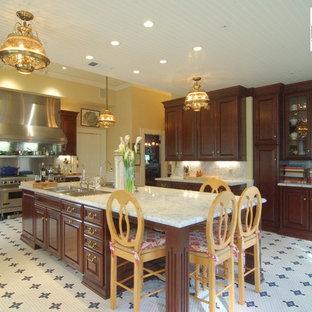 サンルイスオビスポのヴィクトリアン調のおしゃれなキッチン (ドロップインシンク、レイズドパネル扉のキャビネット、濃色木目調キャビネット、大理石カウンター、白いキッチンパネル、石スラブのキッチンパネル、シルバーの調理設備) の写真