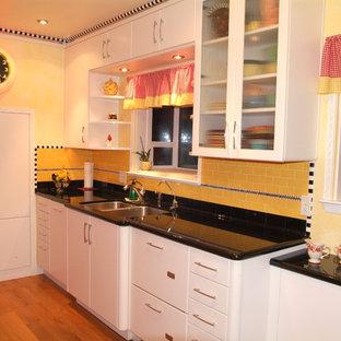 Geschlossene, Zweizeilige, Kleine Eklektische Küche ohne Insel mit Unterbauwaschbecken, flächenbündigen Schrankfronten, weißen Schränken, Granit-Arbeitsplatte, Küchenrückwand in Gelb, Rückwand aus Keramikfliesen, bunten Elektrogeräten und hellem Holzboden in San Luis Obispo