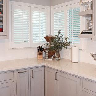 サンフランシスコの大きいシャビーシック調のおしゃれなキッチン (エプロンフロントシンク、シェーカースタイル扉のキャビネット、グレーのキャビネット、珪岩カウンター、白いキッチンパネル、サブウェイタイルのキッチンパネル、シルバーの調理設備の、濃色無垢フローリング、茶色い床、白いキッチンカウンター) の写真