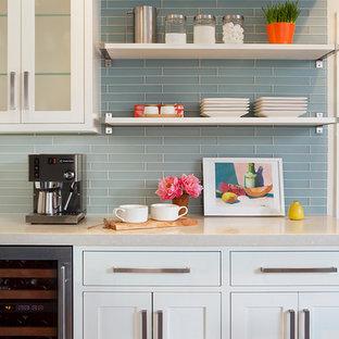 Bild på ett vintage kök, med en rustik diskho, skåp i shakerstil, vita skåp, bänkskiva i kvarts, blått stänkskydd, stänkskydd i glaskakel, rostfria vitvaror, klinkergolv i keramik och en köksö