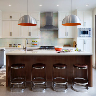 Transitional eat-in kitchen pictures - Example of a transitional l-shaped ceramic floor eat-in kitchen design in San Francisco with a farmhouse sink, shaker cabinets, white cabinets, quartz countertops, blue backsplash, cement tile backsplash, stainless steel appliances and an island