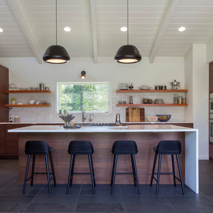 Midcentury open plan kitchen in San Francisco with flat-panel cabinets, dark wood cabinets, white splashback, subway tile splashback, stainless steel appliances, with island, grey floor and slate floors.