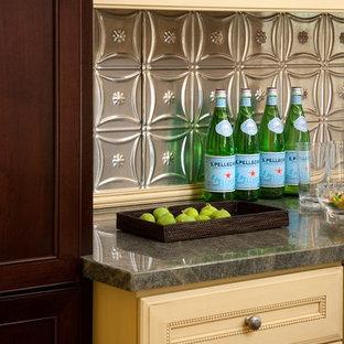 Idee per una grande cucina tradizionale con ante gialle, paraspruzzi grigio, paraspruzzi con piastrelle di metallo e pavimento in legno massello medio