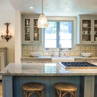 Inspiration for a traditional kitchen in Santa Barbara with a farmhouse sink, glass-front cabinets, grey cabinets, beige splashback and panelled appliances.