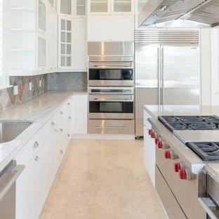 他の地域の大きいビーチスタイルのおしゃれなキッチン (ドロップインシンク、シェーカースタイル扉のキャビネット、白いキャビネット、御影石カウンター、マルチカラーのキッチンパネル、スレートのキッチンパネル、シルバーの調理設備、トラバーチンの床、ベージュの床、マルチカラーのキッチンカウンター) の写真