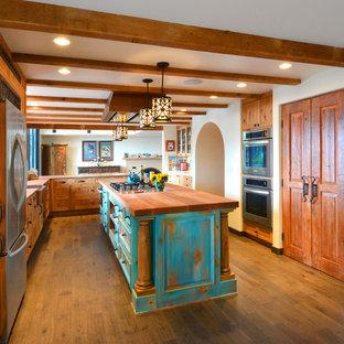 Bild på ett stort amerikanskt kök, med en rustik diskho, luckor med infälld panel, turkosa skåp, träbänkskiva, flerfärgad stänkskydd, stänkskydd i keramik, rostfria vitvaror, mellanmörkt trägolv, en köksö och brunt golv