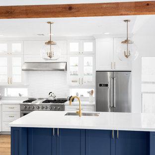 ヒューストンの中くらいのトランジショナルスタイルのおしゃれなキッチン (アンダーカウンターシンク、落し込みパネル扉のキャビネット、青いキャビネット、クオーツストーンカウンター、白いキッチンパネル、サブウェイタイルのキッチンパネル、シルバーの調理設備、淡色無垢フローリング、オレンジの床、白いキッチンカウンター) の写真