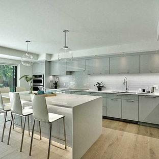 Foto di una grande cucina design con lavello sottopiano, ante a persiana, ante grigie, top in quarzo composito, paraspruzzi bianco, paraspruzzi con piastrelle diamantate, elettrodomestici in acciaio inossidabile, parquet chiaro, isola e pavimento grigio