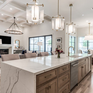 Offene, Geräumige Klassische Küche mit Unterbauwaschbecken, Schrankfronten im Shaker-Stil, Quarzwerkstein-Arbeitsplatte, Küchengeräten aus Edelstahl, hellem Holzboden, Kücheninsel, beigem Boden, weißer Arbeitsplatte und hellbraunen Holzschränken in Houston