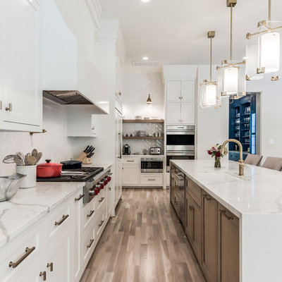 Example of a huge transitional l-shaped light wood floor and beige floor open concept kitchen design in Houston with an undermount sink, shaker cabinets, light wood cabinets, quartz countertops, white backsplash, subway tile backsplash, stainless steel appliances, an island and white countertops