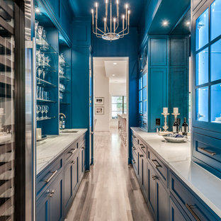 ヒューストンの巨大なトランジショナルスタイルのおしゃれなキッチン (アンダーカウンターシンク、シェーカースタイル扉のキャビネット、青いキャビネット、クオーツストーンカウンター、メタリックのキッチンパネル、ミラータイルのキッチンパネル、シルバーの調理設備の、淡色無垢フローリング、ベージュの床、白いキッチンカウンター) の写真