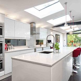 Идея дизайна: параллельная кухня-гостиная среднего размера в современном стиле с врезной раковиной, плоскими фасадами, белыми фасадами, техникой из нержавеющей стали и островом
