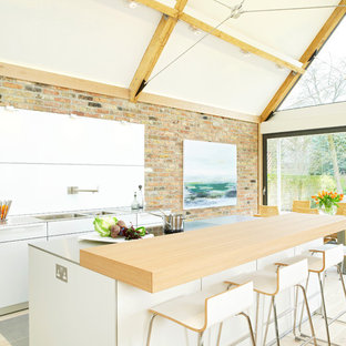 Medium sized contemporary single-wall kitchen in Hampshire with a double-bowl sink, flat-panel cabinets, white cabinets, beige floors, wood worktops, white splashback, stainless steel appliances, light hardwood flooring and an island.