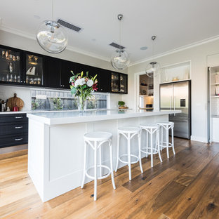 Inspiration for a transitional kitchen in Melbourne with shaker cabinets, black cabinets, window splashback, stainless steel appliances, medium hardwood floors, with island, brown floor and white benchtop.