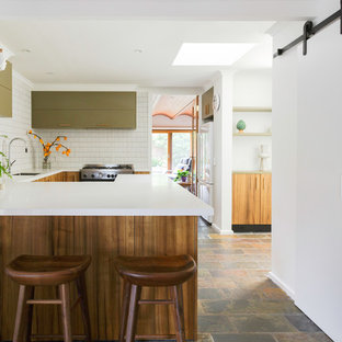 This is an example of a large contemporary u-shaped kitchen in Melbourne with green cabinets, solid surface benchtops, white splashback, stainless steel appliances, limestone floors, white benchtop, an undermount sink, flat-panel cabinets, matchstick tile splashback and a peninsula.