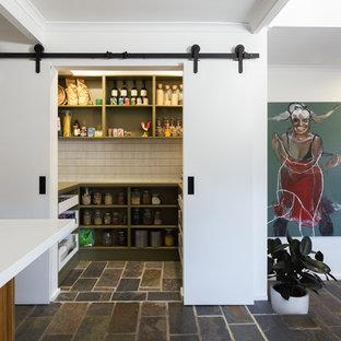 Идея дизайна: большая п-образная кухня в современном стиле с кладовкой, накладной раковиной, фасадами с декоративным кантом, зелеными фасадами, столешницей из акрилового камня, белым фартуком, фартуком из плитки кабанчик, техникой из нержавеющей стали, полом из известняка, островом и белой столешницей