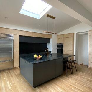 ボルチモアの中くらいのモダンスタイルのおしゃれなキッチン (アンダーカウンターシンク、フラットパネル扉のキャビネット、淡色木目調キャビネット、御影石カウンター、黒いキッチンパネル、御影石のキッチンパネル、シルバーの調理設備、無垢フローリング、茶色い床、黒いキッチンカウンター、三角天井) の写真