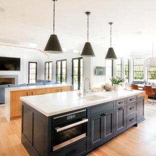 ニューヨークの広いトランジショナルスタイルのおしゃれなキッチン (エプロンフロントシンク、フラットパネル扉のキャビネット、白いキャビネット、珪岩カウンター、白いキッチンパネル、石スラブのキッチンパネル、シルバーの調理設備、淡色無垢フローリング、黄色い床、白いキッチンカウンター) の写真
