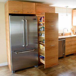 ボストンの小さいインダストリアルスタイルのおしゃれなキッチン (フラットパネル扉のキャビネット、中間色木目調キャビネット、御影石カウンター、シルバーの調理設備の、アイランドなし) の写真