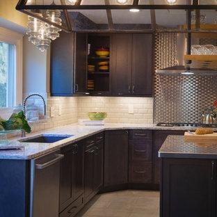 デトロイトの中サイズのインダストリアルスタイルのおしゃれなキッチン (アンダーカウンターシンク、シェーカースタイル扉のキャビネット、濃色木目調キャビネット、珪岩カウンター、白いキッチンパネル、セラミックタイルのキッチンパネル、シルバーの調理設備の、磁器タイルの床、ベージュの床) の写真