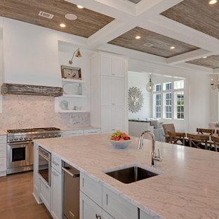 Exemple d'une très grande cuisine ouverte exotique en L avec un évier 2 bacs, un placard avec porte à panneau encastré, des portes de placard blanches, un plan de travail en marbre, une crédence blanche, un électroménager en acier inoxydable, un sol en bois foncé, un îlot central, une crédence en marbre et un sol beige.