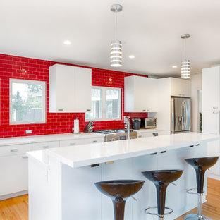 オレンジカウンティの大きいモダンスタイルのおしゃれなキッチン (アンダーカウンターシンク、フラットパネル扉のキャビネット、白いキャビネット、クオーツストーンカウンター、赤いキッチンパネル、ガラスタイルのキッチンパネル、シルバーの調理設備の、無垢フローリング、茶色い床、白いキッチンカウンター) の写真