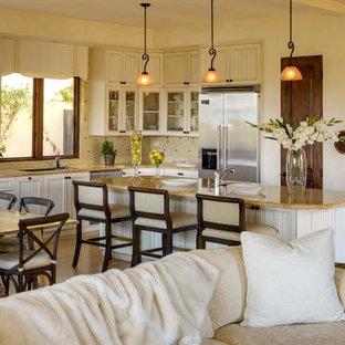 Свежая идея для дизайна: угловая кухня-гостиная среднего размера в средиземноморском стиле с врезной раковиной, бежевыми фасадами, столешницей из гранита, бежевым фартуком, техникой из нержавеющей стали, фасадами с декоративным кантом, фартуком из керамической плитки, полом из бамбука, островом и бежевой столешницей - отличное фото интерьера