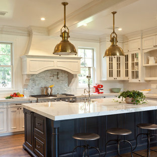 Large traditional eat-in kitchen inspiration - Eat-in kitchen - large traditional u-shaped dark wood floor eat-in kitchen idea in Santa Barbara with a farmhouse sink, recessed-panel cabinets, white cabinets, marble countertops, white backsplash, stainless steel appliances and an island