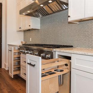 オースティンの大きい地中海スタイルのおしゃれなキッチン (ダブルシンク、シェーカースタイル扉のキャビネット、黄色いキャビネット、ベージュキッチンパネル、セラミックタイルのキッチンパネル、シルバーの調理設備、無垢フローリング、茶色い床) の写真