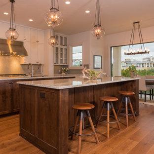 オースティンの大きい地中海スタイルのおしゃれなキッチン (ダブルシンク、シェーカースタイル扉のキャビネット、黄色いキャビネット、ベージュキッチンパネル、セラミックタイルのキッチンパネル、シルバーの調理設備の、無垢フローリング、茶色い床) の写真