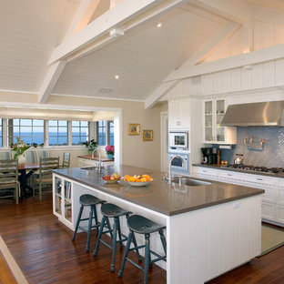 This is an example of a large traditional galley open plan kitchen in Santa Barbara with a single-bowl sink, quartz benchtops, blue splashback, glass-front cabinets, white cabinets, glass tile splashback, stainless steel appliances, with island and dark hardwood floors.