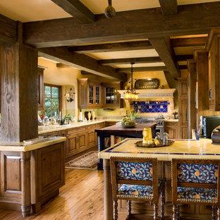 サンタバーバラの地中海スタイルのおしゃれなキッチン (中間色木目調キャビネット、タイルカウンター、青いキッチンパネル、黄色いキッチンカウンター) の写真