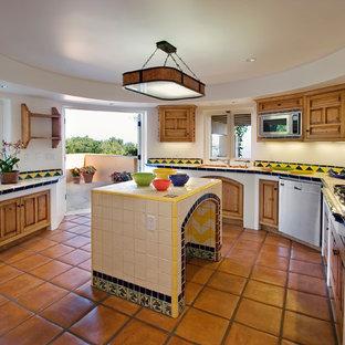 Medelhavsstil inredning av ett avskilt kök, med en undermonterad diskho, luckor med infälld panel, skåp i mellenmörkt trä, kaklad bänkskiva, flerfärgad stänkskydd, stänkskydd i keramik, rostfria vitvaror och klinkergolv i terrakotta