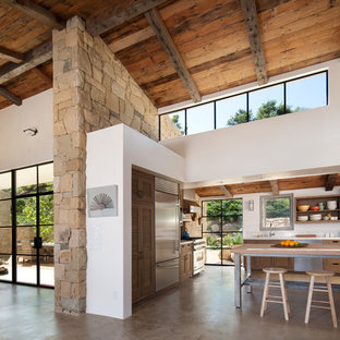 Mediterranean eat-in kitchen ideas - Eat-in kitchen - mediterranean l-shaped concrete floor and gray floor eat-in kitchen idea in Santa Barbara with louvered cabinets, dark wood cabinets, white backsplash, stainless steel appliances and an island
