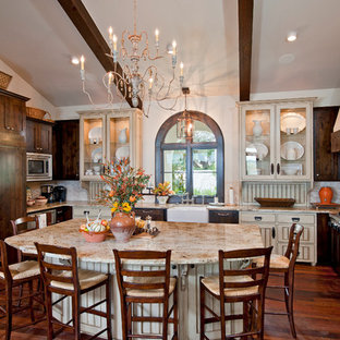 Large tuscan u-shaped dark wood floor and brown floor open concept kitchen photo in Austin with a farmhouse sink, dark wood cabinets, paneled appliances, glass-front cabinets, granite countertops, white backsplash and an island
