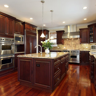 Inspiration for a timeless u-shaped eat-in kitchen remodel in Philadelphia with an undermount sink, raised-panel cabinets, brown cabinets, granite countertops, beige backsplash, stone slab backsplash and stainless steel appliances
