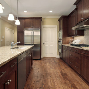Example of a classic galley eat-in kitchen design in Philadelphia with an undermount sink, brown cabinets, granite countertops, beige backsplash and stainless steel appliances