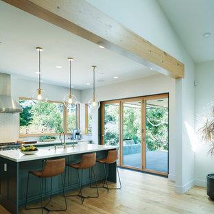 Inspiration för stora moderna vitt kök, med en rustik diskho, skåp i shakerstil, blå skåp, bänkskiva i kvarts, vitt stänkskydd, stänkskydd i keramik, rostfria vitvaror, ljust trägolv och en köksö