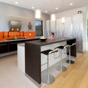 他の地域のエクレクティックスタイルのおしゃれなアイランドキッチン (フラットパネル扉のキャビネット、オレンジのキッチンパネル、グレーの床、グレーのキッチンカウンター) の写真