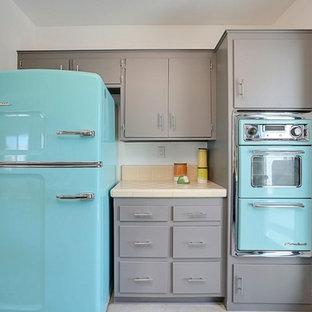 フェニックスの小さいミッドセンチュリースタイルのおしゃれなキッチン (一体型シンク、フラットパネル扉のキャビネット、グレーのキャビネット、タイルカウンター、オレンジのキッチンパネル、磁器タイルのキッチンパネル、カラー調理設備、コンクリートの床) の写真