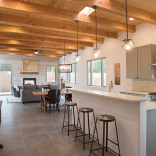Southwestern open concept kitchen pictures - Inspiration for a southwestern gray floor open concept kitchen remodel in Albuquerque with shaker cabinets, gray cabinets, white backsplash, glass tile backsplash, stainless steel appliances, an island and white countertops